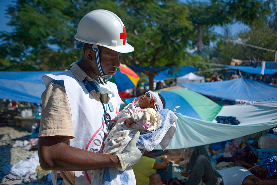 Haitian Red Cross volunteer Jean Zacharie delivers first aid to 1 month old-  Deborah Fatima, mother died in quake.