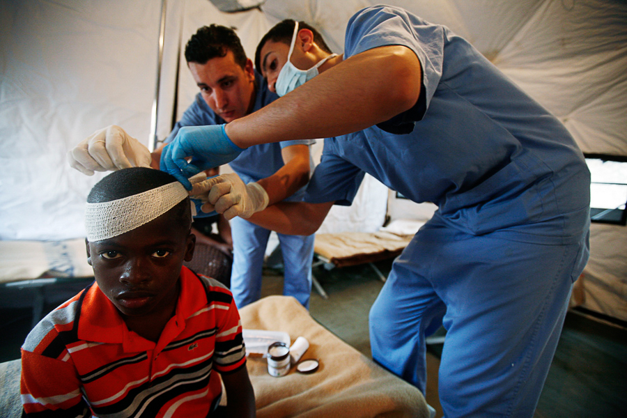 In this photo released by MINUSTAH, an injured youth is attended by medics in a field hospital at the Jordanian battalion's base in Port-au-Prince, Tuesday, Jan. 19, 2010. The U.N. Security Council approved extra troops and police officers to beef up security in Haiti and ensure that desperately needed aid gets to earthquake victims. A 7.0-magnitude earthquake struck Haiti on Jan. 12. (AP Photo/MINUSTAH,Sophia Paris)
